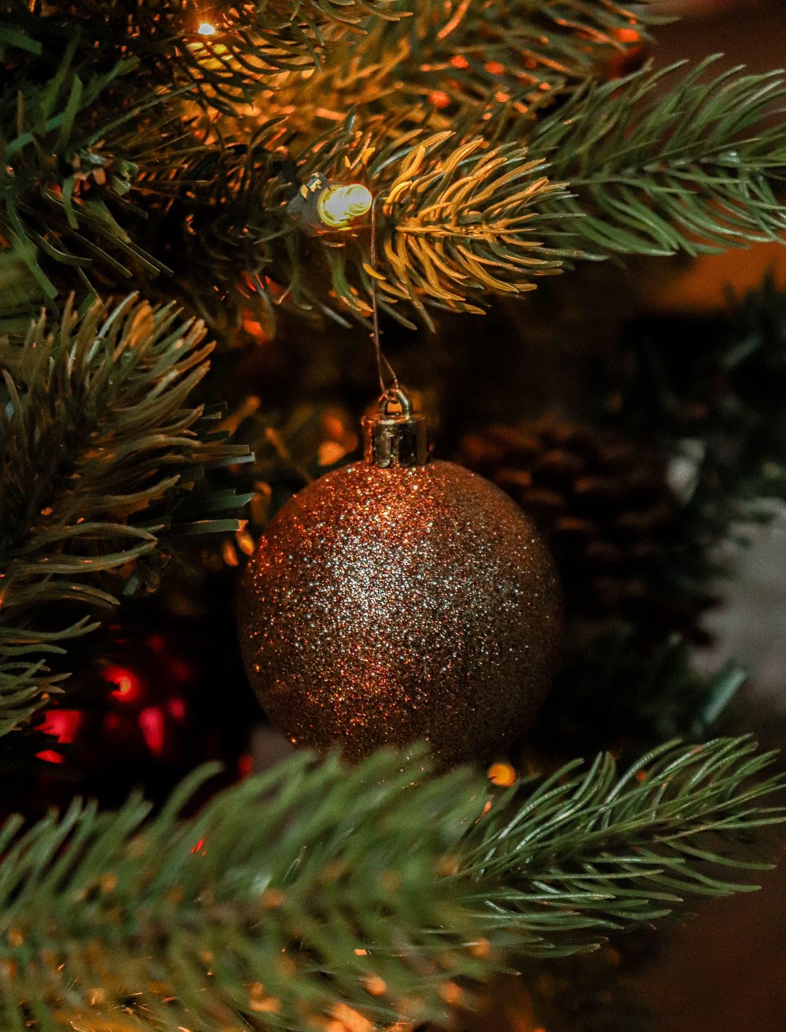 sparkly Christmas ball on Christmas tree with lights