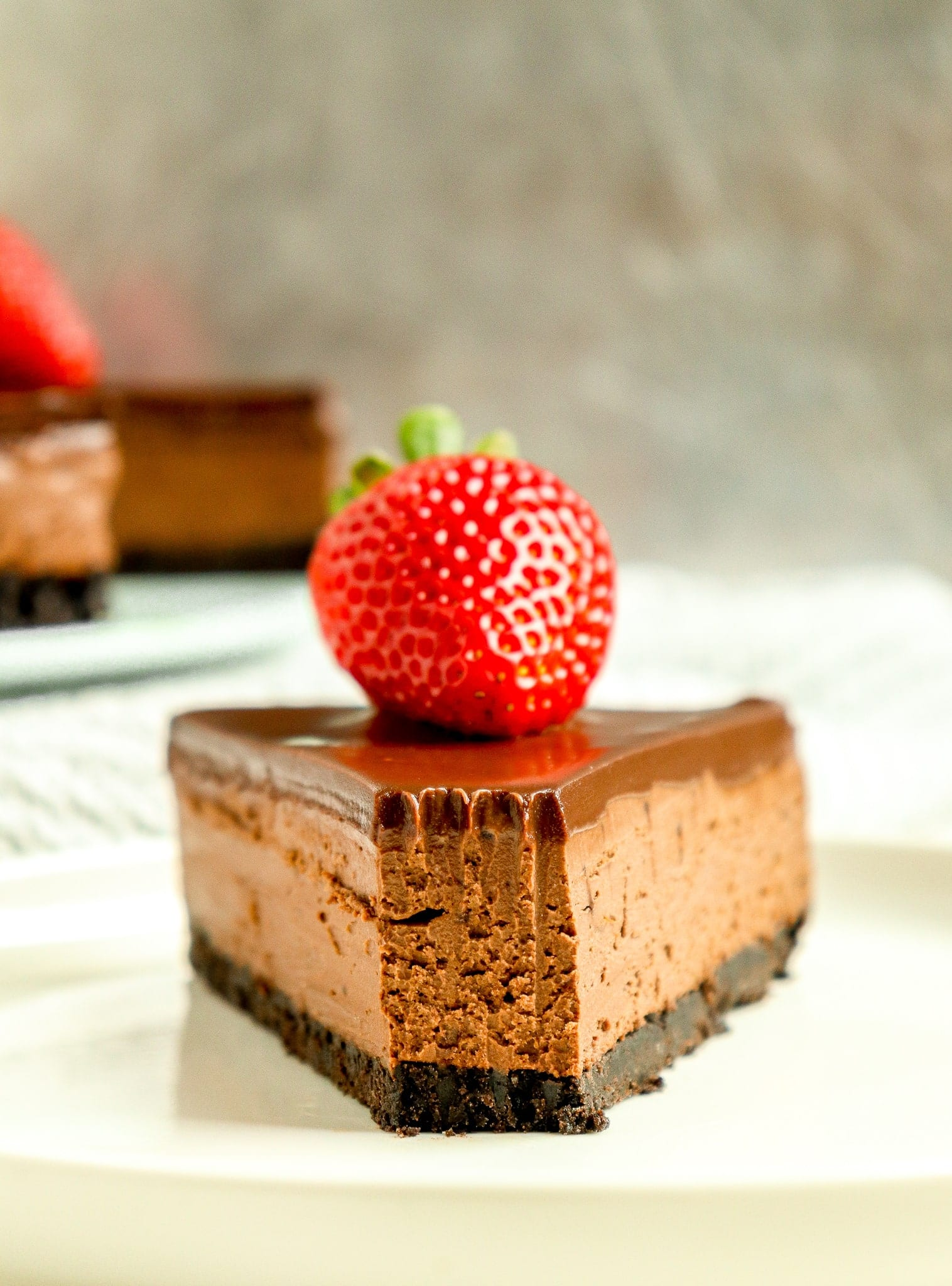 slice of triple chocolate cheesecake with a strawberry on top
