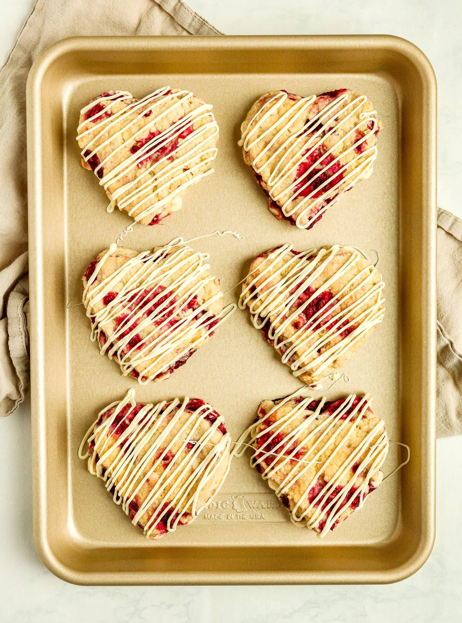 white chocolate raspberry scones with white chocolate drizzle on a gold baking pan