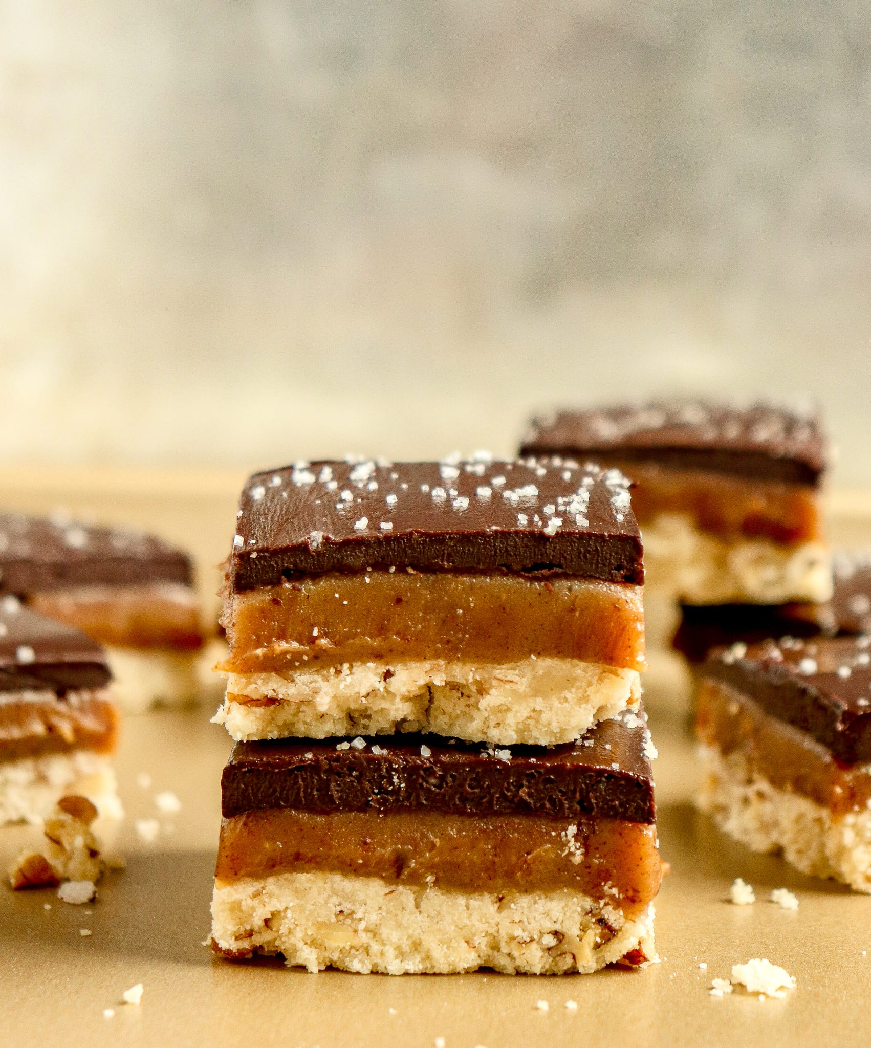stack of pecan caramel shortbread bars topped with dark chocolate ganache and sea salt